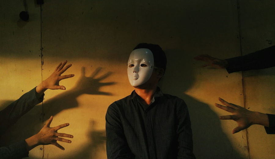 Cropped Hands With Man Wearing Mask Against Wall