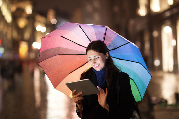 Bokeh Caucasian City Computer Electronics  Evening Girl Horizontal Outdoor Pad Rain Street Tablet Touch Pad Touchscreen Umbrella Urban Use Woman