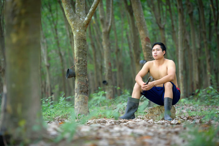 Full length of thoughtful shirtless man sitting in forest