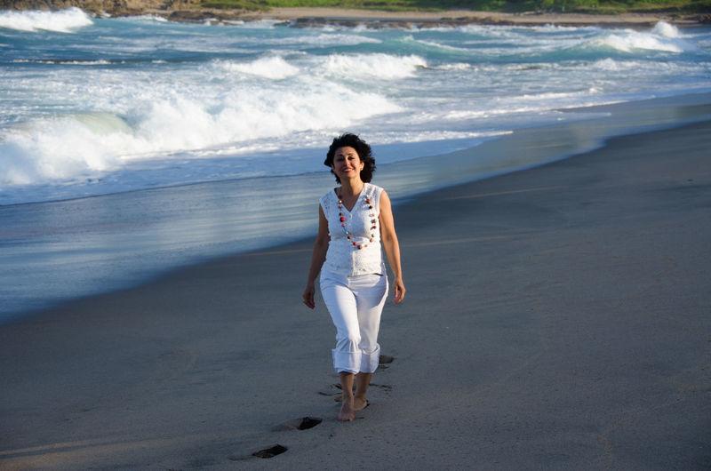 Portrait Smiling Mid Adult Woman Walking On Sandy Beach