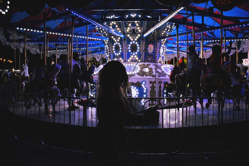 Rear view of woman in illuminated carousel at amusement park