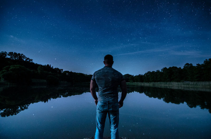 Rear view of man standing in lake against sky at night