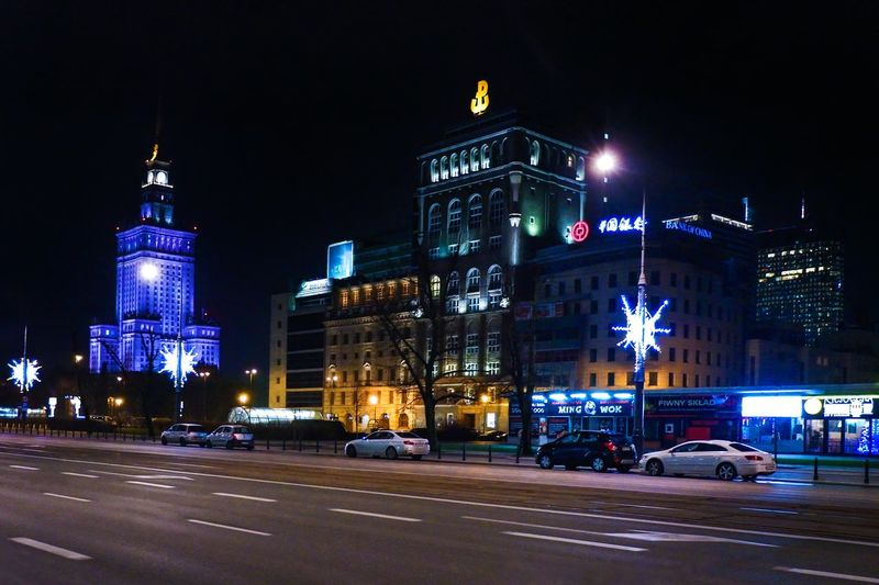 Cars on road by illuminated buildings against sky at night