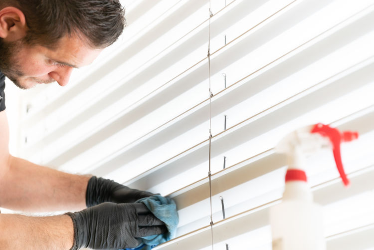 Low angle view of man cleaning window binds