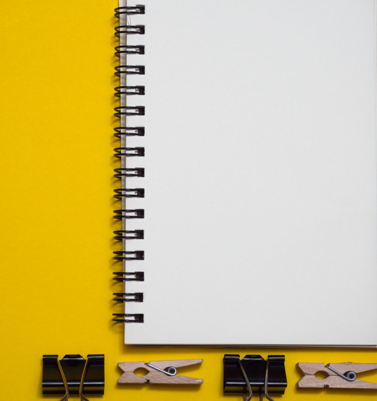 yellow, copy space, indoors, no people, still life, table, office, high angle view, spiral notebook, technology, note pad, business, office supply, paper, close-up, studio shot, publication, book, pen, connection, keyboard instrument