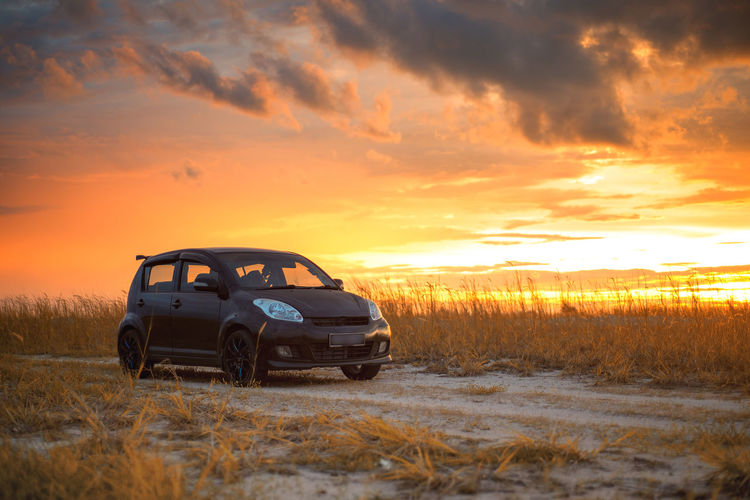 Car on field against sky during sunset