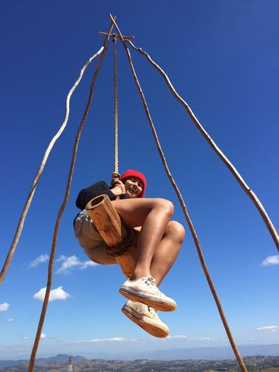 Low angle view of woman enjoying on rope swing against blue sky