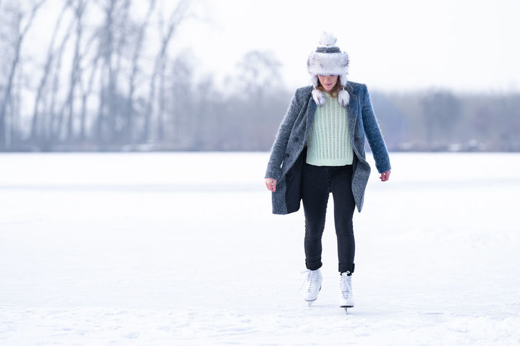 Full length portrait of woman standing in snow