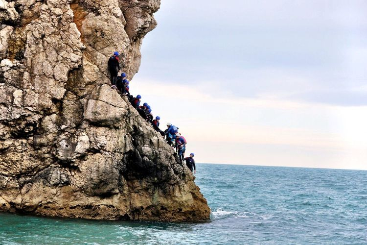 People on rock formation by sea against sky