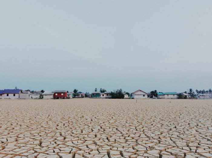 Drought land in town against sky