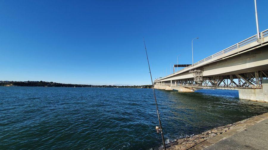 Bridge over sea against clear blue sky