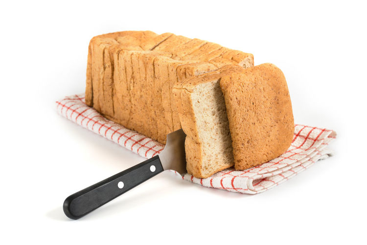 Sliced bread. Baked Bread Breakfast Brown Bread Close-up Cut Out Cutting Board Food Food And Drink Freshness Healthy Eating Indoors  Kitchen Knife Loaf Of Bread No People SLICE Sliced Bread Studio Shot White Background Whole Wheat Bread