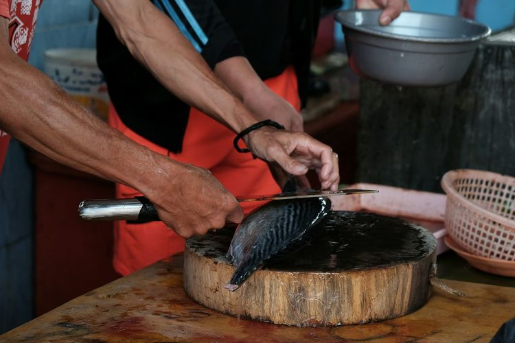 Cropped Hand Of Man Cutting Fish On Board