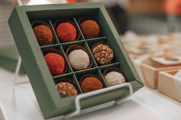 Assorted handmade truffle chocolates candies made from organic ingredients in the gift box.