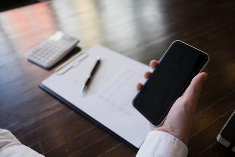 Cropped hand of businessman using mobile phone on desk in office