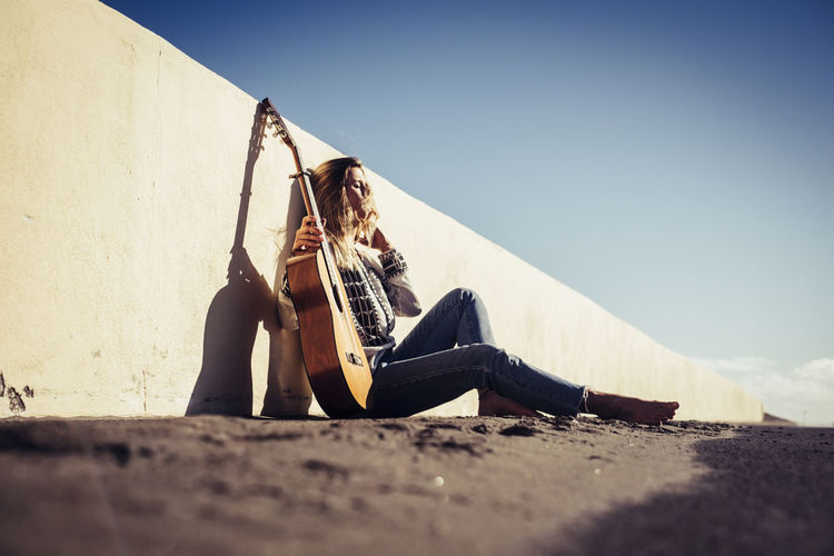 Full length of young woman with guitar leaning on retaining wall against clear sky