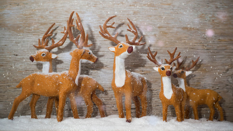 Figures of deers in front of wooden background - it is snowing