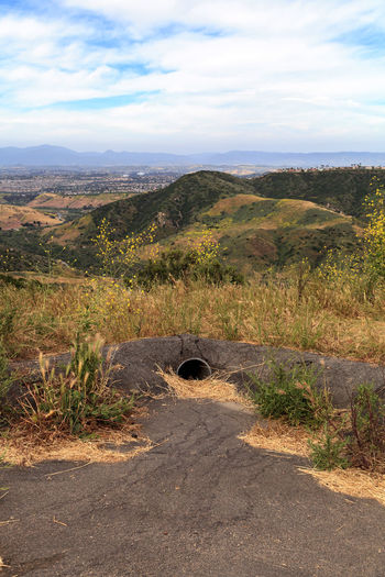 Water drainage set up in a hillside at the Aliso and Wood Canyons Wilderness Park in Laguna Beach, California in spring Beauty In Nature Day Drainage Drainage Channel Drainage Pipes Laguna Beach Landscape Mountain Nature No People Outdoors Road Scenics Sky The Way Forward Tranquility Transportation Tree Water Drain