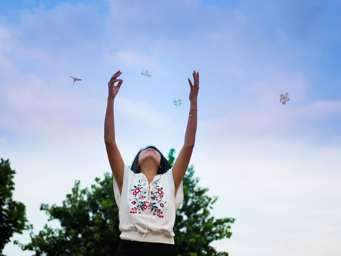 Woman Throwing Flowers Against Sky