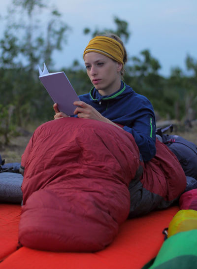young caucasian female reading book while outdoor camping Backpacking Camping Hiking Nature Reading Travel Trekking Woman Book Casual Clothing Caucasian Communication Connection Day Digital Tablet Education Female Focus On Foreground Girl Hikingadventures Hobby Holding Leisure Activity Lifestyles Looking Men Nature One Person Outdoors Paper People person Real People Relaxation Sitting Technology Tent Three Quarter Length Vacation Wireless Technology