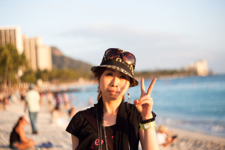 Close-up portrait of woman showing peace sign while standing at beach