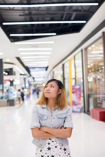 Thoughtful Young Woman Standing In Store