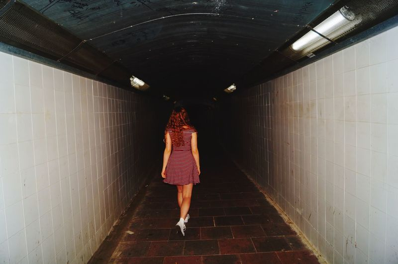 Rear view of woman walking in illuminated tunnel