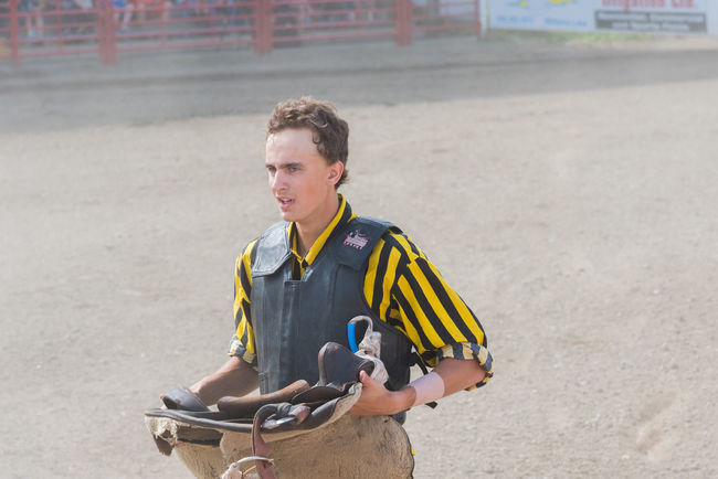 Williams Lake, British Columbia/Canada - July 2, 2016: a teammate at the Wild Horse Race stands ready with a saddle while his team tries to catch the horse, during the 90th Williams Lake Stampede 90th Williams Lake Stampede Arena British Columbia, Canada Cariboo Chilcotin Cowboy Man Saddle Waiting Wild Horse Race Candid Dangerous Documentary Dust Editorial  Extreme Sport Male Outdoors person Professional Rodeo Race RISK Rodeo Sport Stampede Watching