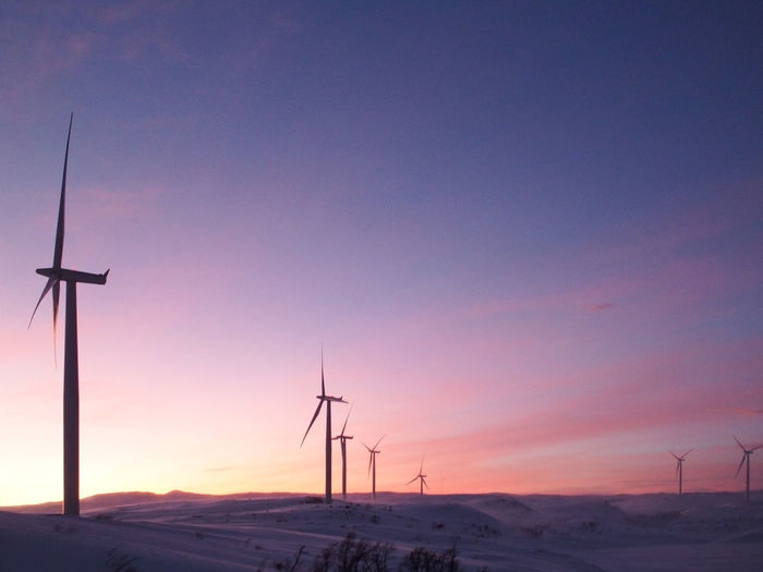 Wind turbines on landscape at sunset