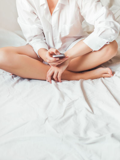 Midsection of woman using mobile phone while sitting on bed
