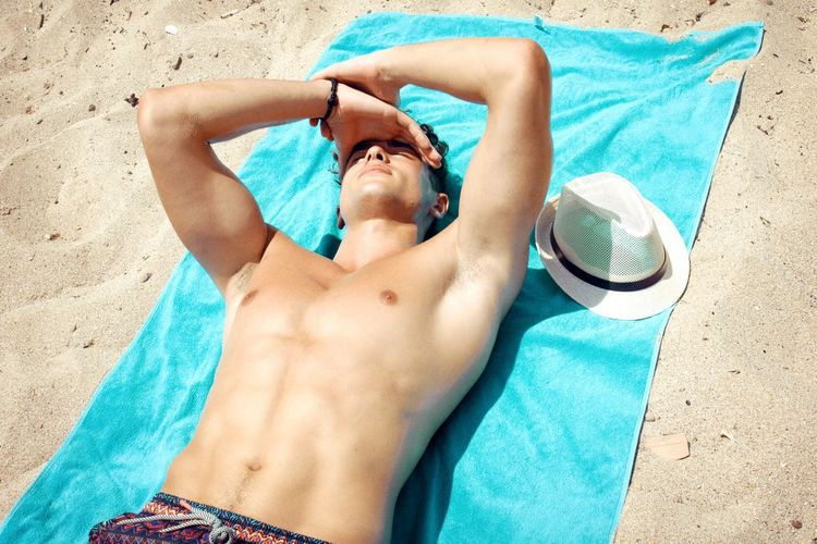 Shirtless man relaxing at beach in sunny day