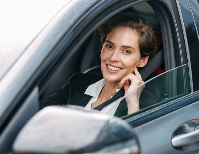 Portrait of smiling businesswoman sitting in car