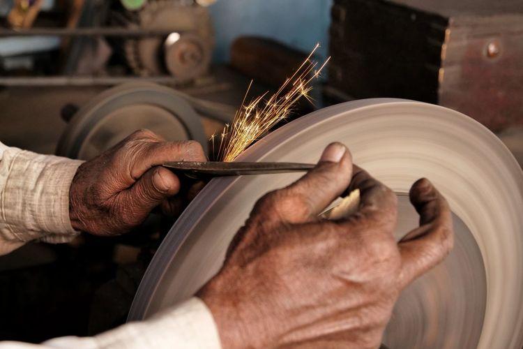 Cropped image of man sharpening knife
