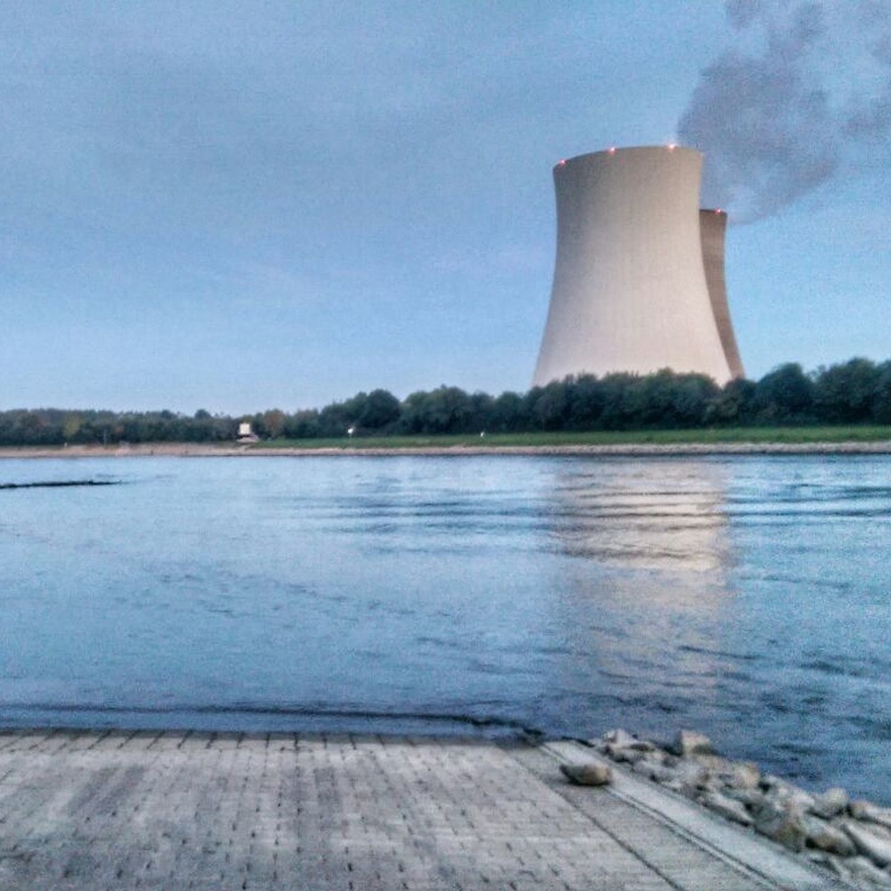 built structure, smoke stack, cooling tower, no people, outdoors, water, architecture, day, industry, lake, power station, building exterior, fuel and power generation, sky, tree, nature