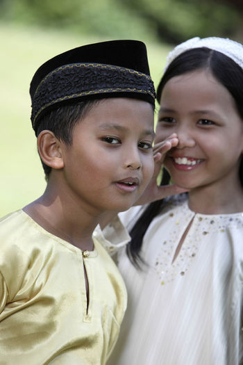 malay kids with traditional clothing whispering Baju Melayu Hari Raya Aidilfitri Innocence Ramadan  Traditional Clothing Whispering Baju Kurung Boys Child Childhood Cute Different Cultures Elementary Age Friendship Girl Lifestyles Malay Malaysia Outdoors Park - Man Made Space Real People Secret Togetherness Two People