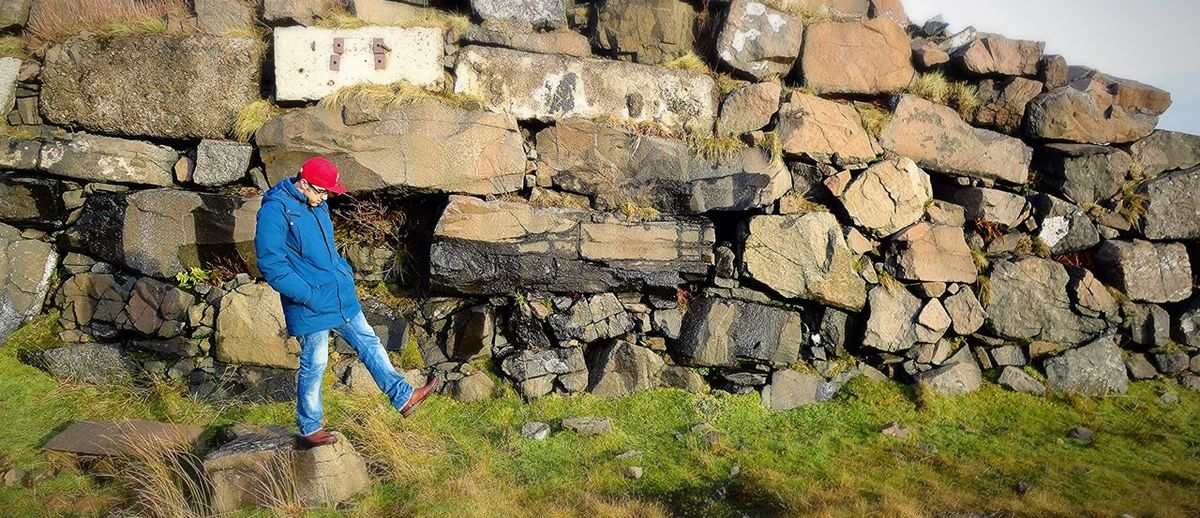 Full length of man kicking on field against stone wall
