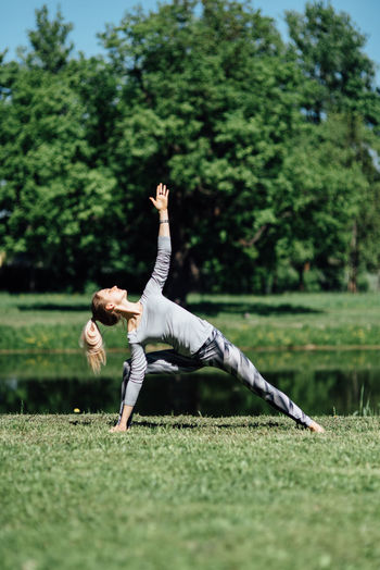 Full length of young woman exercising by pond on field