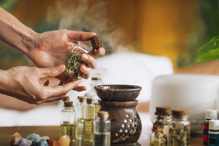 Ayurveda aromatherapy massage, female hand pouring aromatic oil in an essential oil diffuser