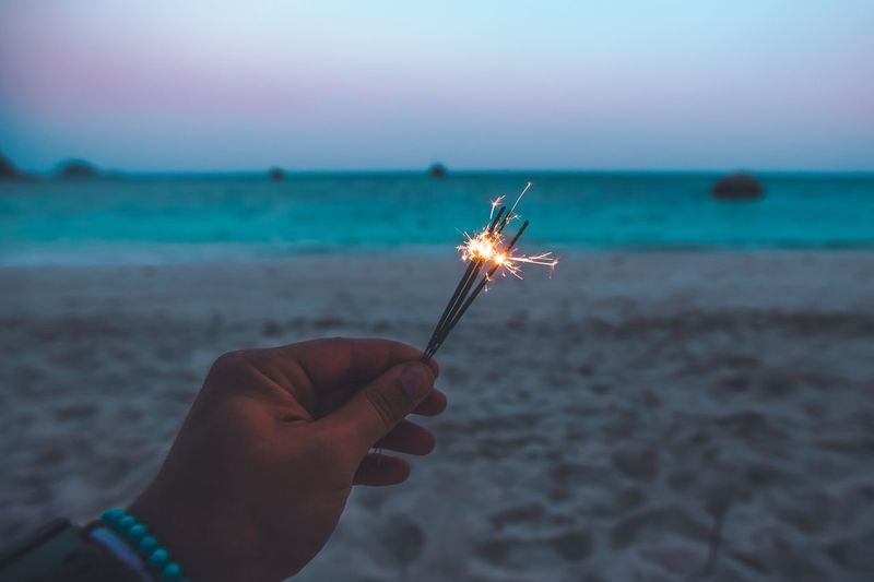 Cropped Hand Holding Sparkler At Beach