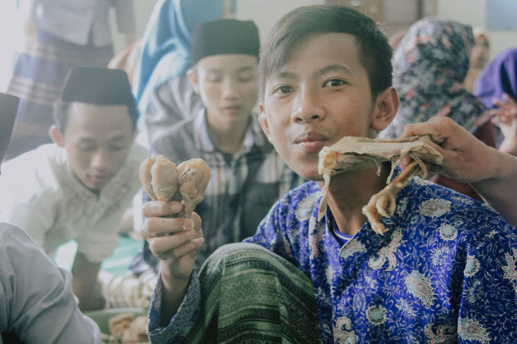 portrait of a boy with his friend in islamic religious activities