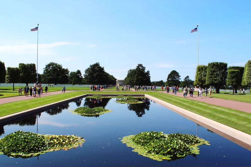 Reflection of people on pond in park against sky
