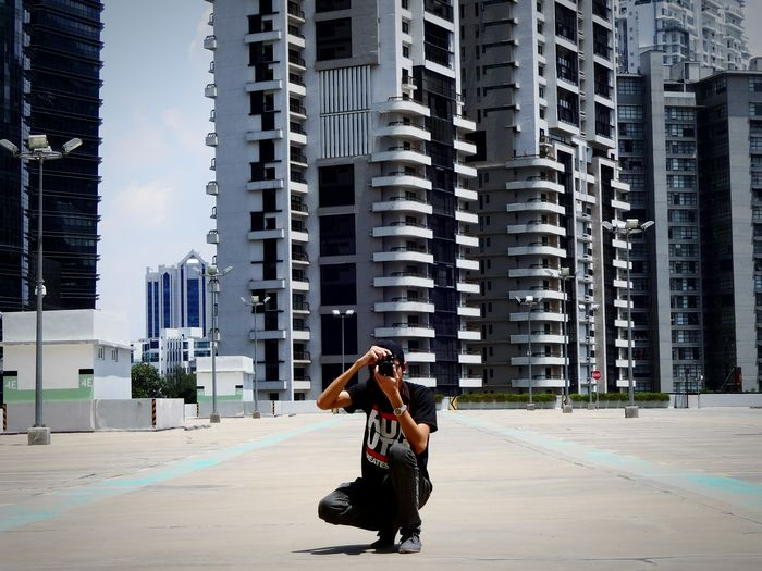 Young Man Photographing With Camera On Road Against Buildings