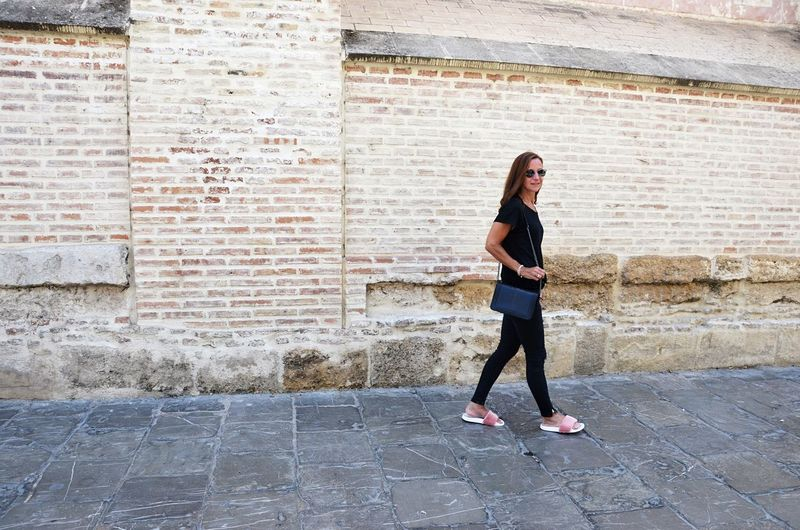Side View Of Woman Walking By Brick Wall