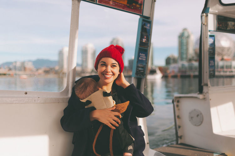 A beautiful young woman smiling while wearing her baby and riding on a ferry boat through the city. Happiness Smiling Portrait Young Women Emotion Warm Clothing Beautiful Woman Happy Baby Baby Wearing Boat Transportation Transit City
