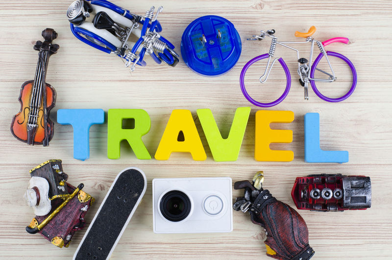 top view vacation and holiday concept word TRAVEL with accessories on wooden background Indoors  Directly Above Large Group Of Objects Wood - Material High Angle View Still Life Equipment Table Text No People Scissors Rope Multi Colored Group Of Objects Capital Letter Preparation  Tape Measure Hand Tool Leisure Activity Hand Saw