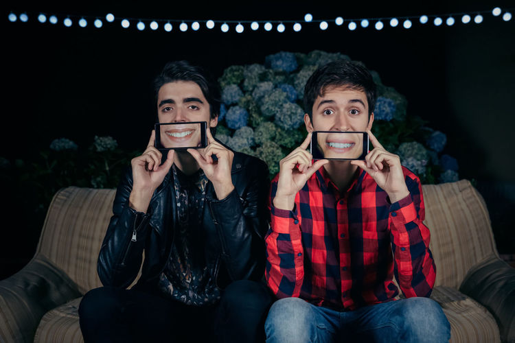 Closeup of two funny young men holding smartphones over their faces showing female mouths smiling in the screen on a outdoors party. Friendship and celebrations concept. Celebration Fun Funny Garland Horizontal Lips Man Mouth Screen Sitting Caucasian Covering Display Female Grimace Male Night Outdoors Party Phone Smartphone Smiling Sofa Togheter Two People