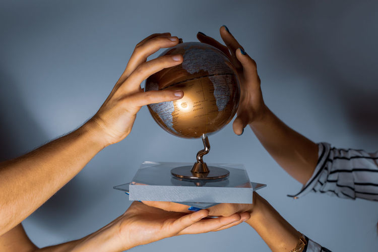 Close-up of people holding globe over blue background