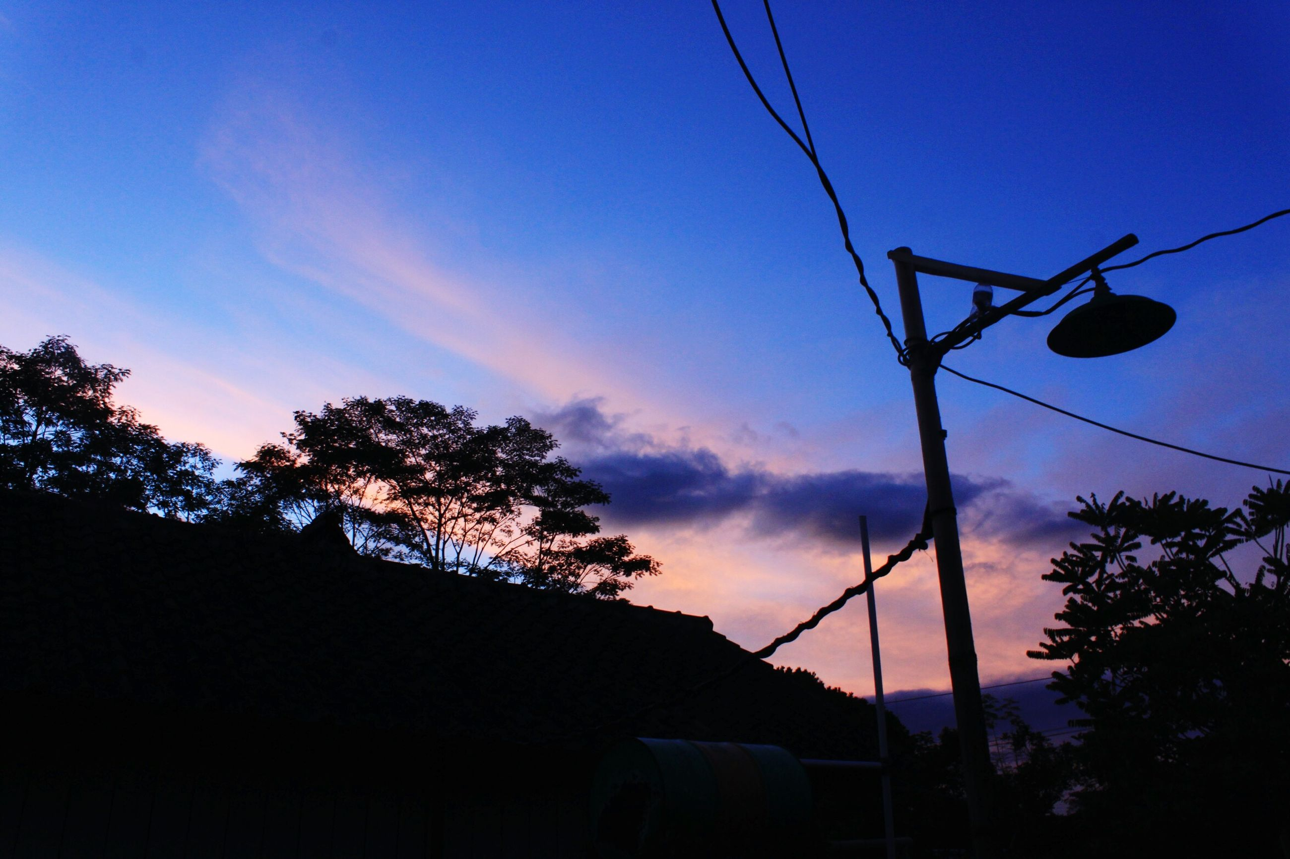 silhouette, low angle view, sunset, power line, sky, tree, electricity pylon, electricity, cable, blue, power supply, street light, dusk, nature, connection, power cable, beauty in nature, outdoors, built structure, tranquility