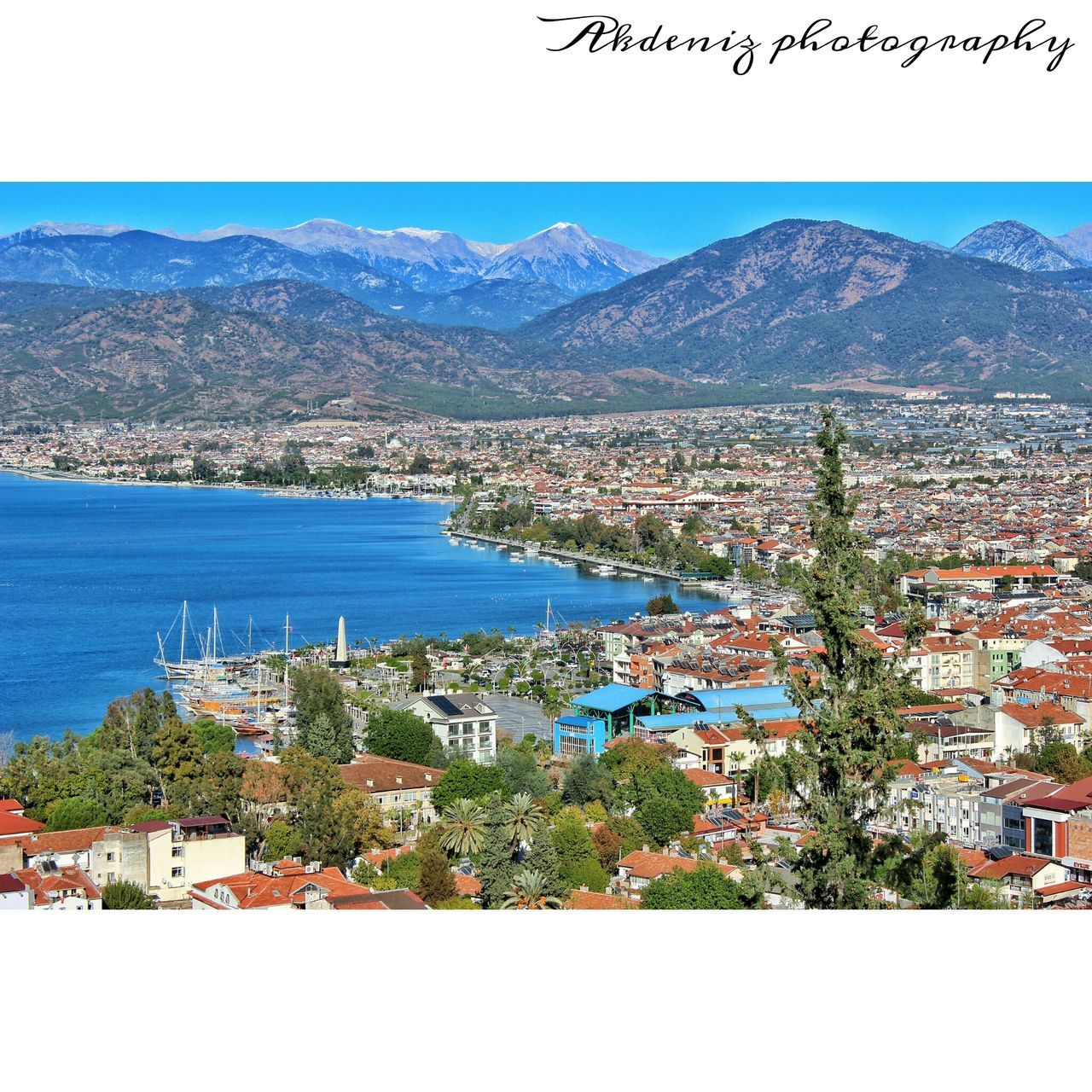 mountain, building exterior, built structure, architecture, town, residential district, house, mountain range, residential building, water, high angle view, day, nature, scenics, no people, sea, outdoors, clear sky, beauty in nature, community, blue, landscape, sky, cityscape, tree, city, view into land