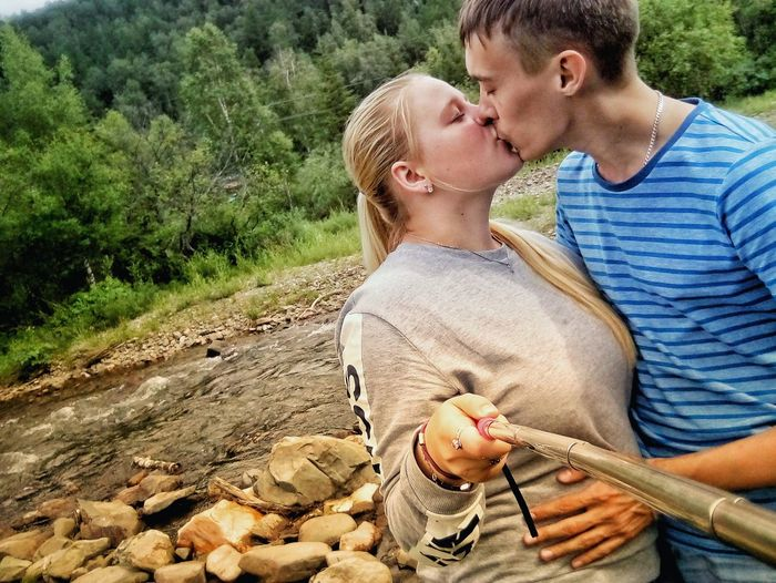 Side View Of Young Couple Kissing While Standing Against Trees In Forest